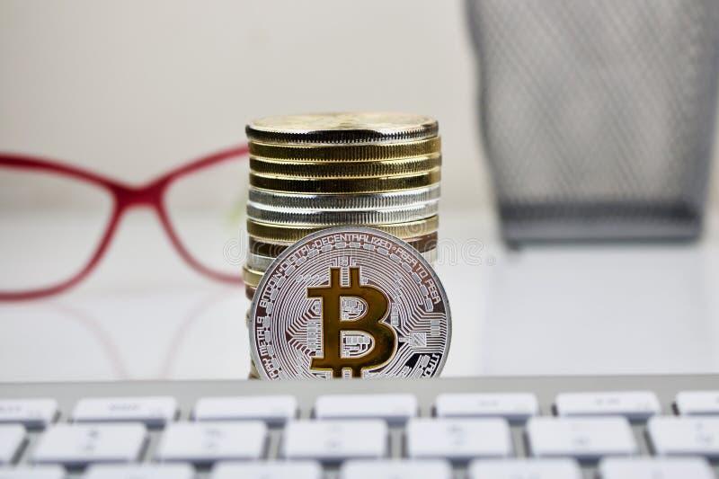 Srebna bitcoin moneta z żółtym b znakiem fotografia royalty free