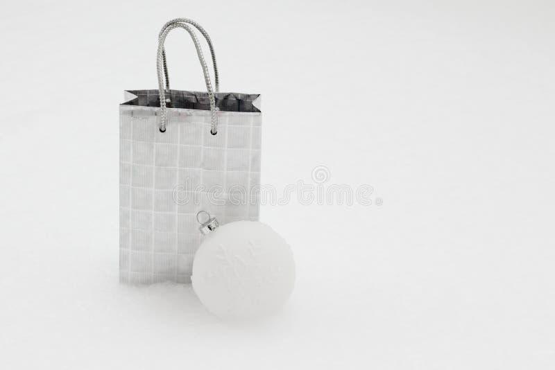 Srebna prezent torba z Bożenarodzeniową piłką w śniegu zdjęcia royalty free