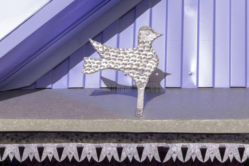 Srebnego metalu ptasia postać na fasadzie stary drewniany dom w Syberia dekoracje zdjęcie royalty free
