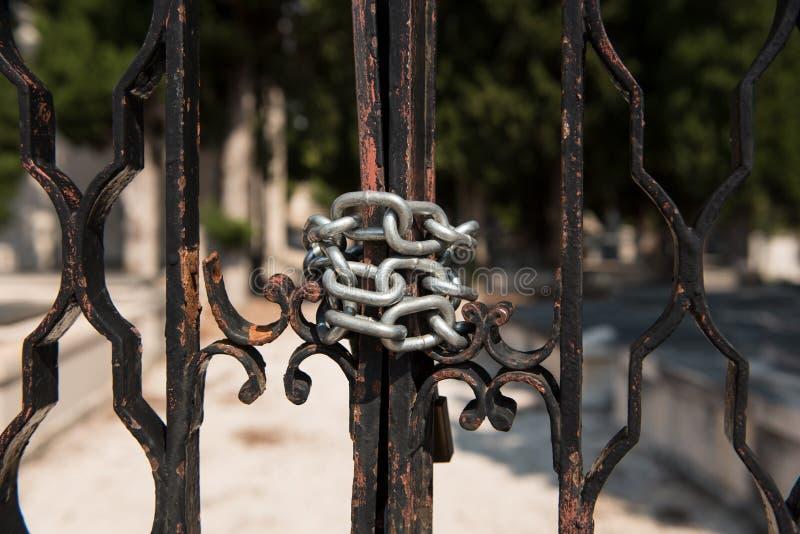 Srebny łańcuch na metalu cmentarza ogrodzeniu Zamknięci starzy metali drzwi z metalu łańcuchem obrazy royalty free