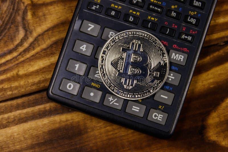 Srebny bitcoin i kalkulator na drewnianym biurku zdjęcia stock