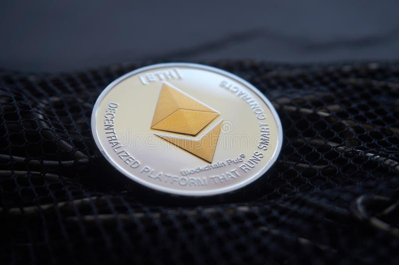 Srebny Ethereum monety lying on the beach na łańcuchu i sieci fotografia stock