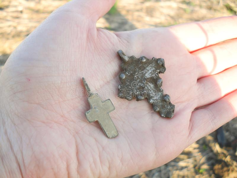 Srebny krzyż w ręce zakłada podczas gdy metalu wykrywać fotografia stock