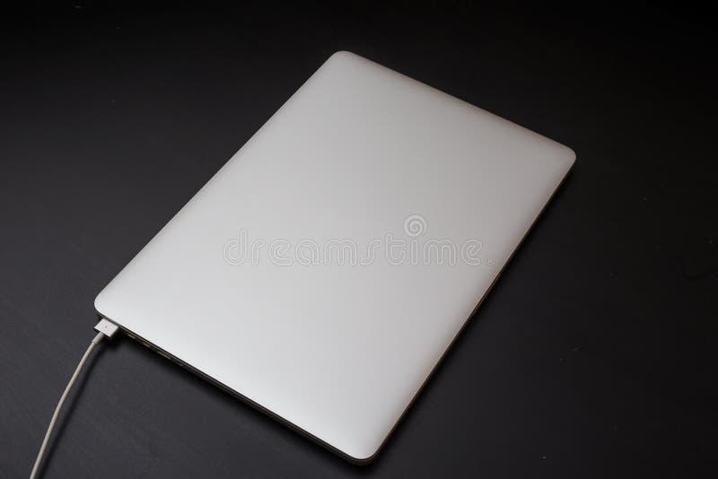 Srebny laptop ładuje magnesowym włącznikiem na czarnym drewnianym tle obrazy stock