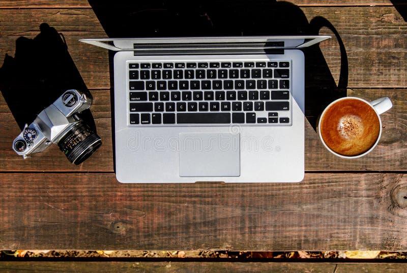 Srebny laptop Outdoors i Foamy Latte na Drewnianym stole zdjęcie stock