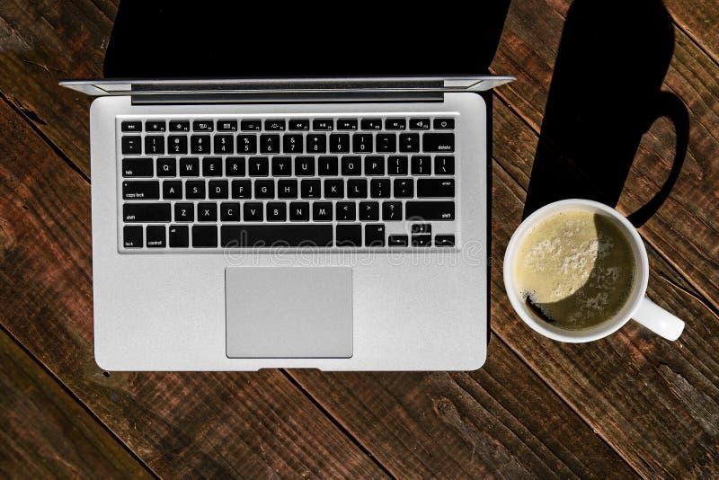 Srebny laptop Outdoors i Foamy Latte na Drewnianym stole obraz stock