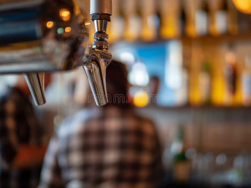 Srebny piwa klepnięcie w restauracja barze z ciężkimi napojami i trunkiem w tle zdjęcia stock