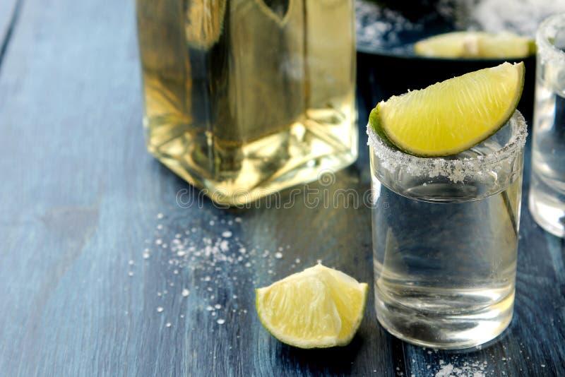 Srebny tequila w szkle z solą i wapnem na błękitnym drewnianym stole napoje alkoholowe zdjęcia stock