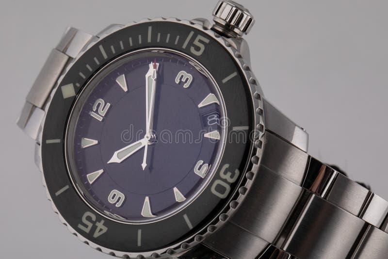 Srebny wristwatch z błękitną tarczą, osrebrza clockwise, chronograf, na metal patce na białym tle fotografia royalty free
