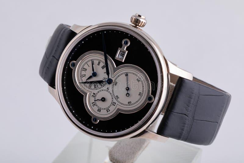 Srebny wristwatch z białą tarczą, czarnym clockwise, stopwatch i chronografem na czarnej rzemiennej patce na białym tle, obrazy royalty free
