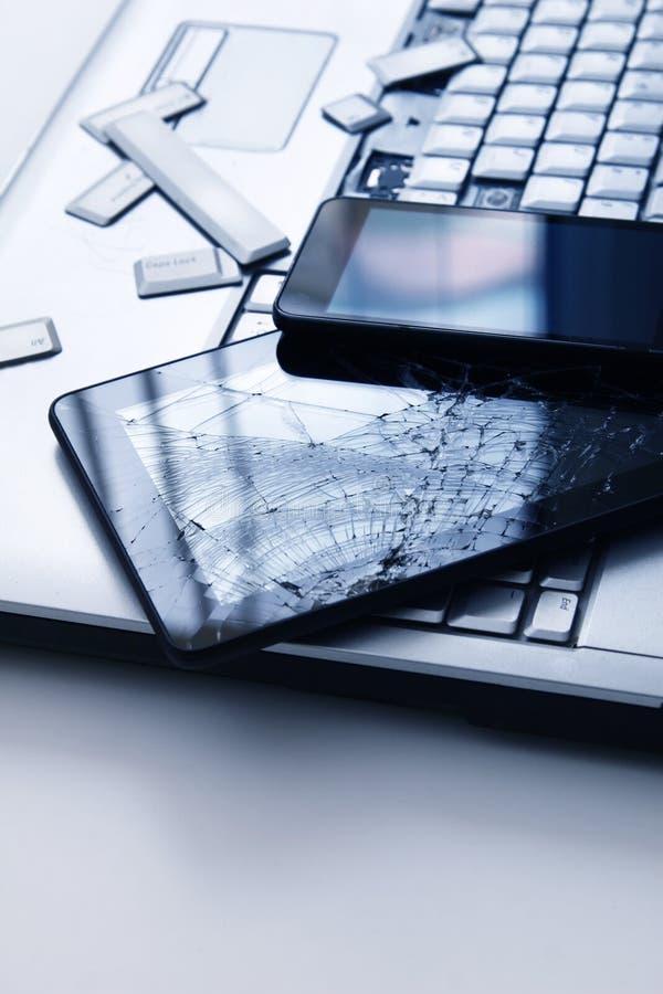 Srebrny notebook z uszkodzoną klawiaturą, tabletem z pękniętym wyświetlaczem i czarnym telefonem Zbliżony obraz części uszkodzone obrazy royalty free