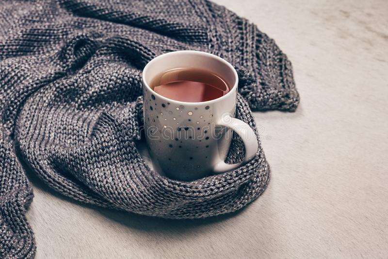 Srebrzysty siwieje trykotową tkaninę wzdłuż filiżanki herbata na milky białym futerkowym tle zdjęcie stock