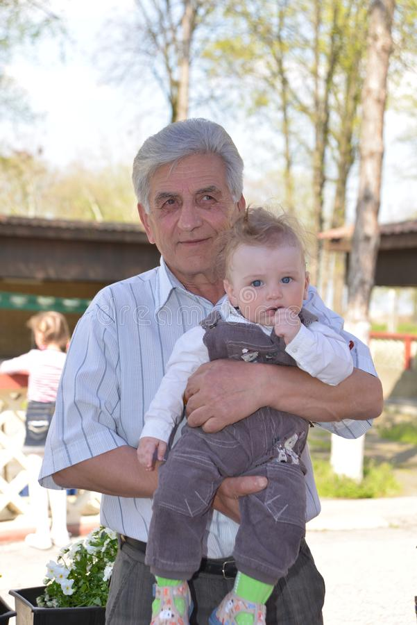 Sremska Mitrovica, Serbia / October 10, 2019: child in the arms of an older man. The child looks forward and holds his hand near royalty free stock photo