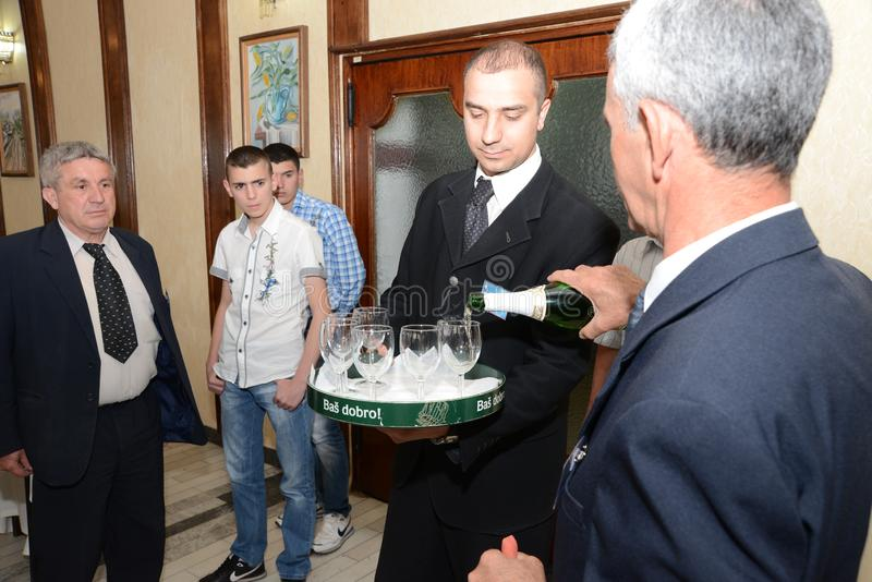 Sremska Mitrovica, Serbia / October 10, 2019: a man pours champagne into wine glasses, other men wait and want to try a drink stock image