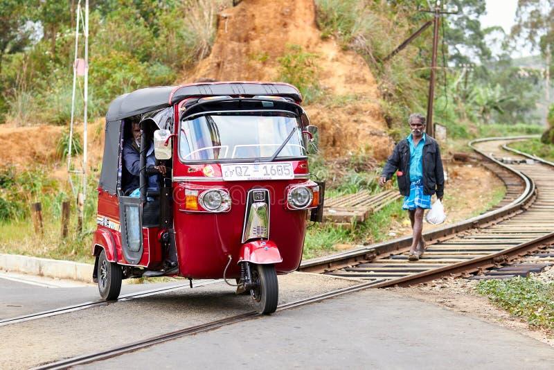 Sri Lanka, Paradeniya, 13 102 2020, ett rött tuk-tuk i centrum av järnvägen arkivbilder