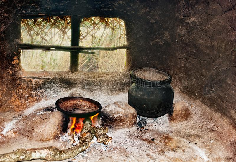 Sri Lanka`s poor people`s kitchen in the hut. A frying pan and a pot on a primitive cooker stock image