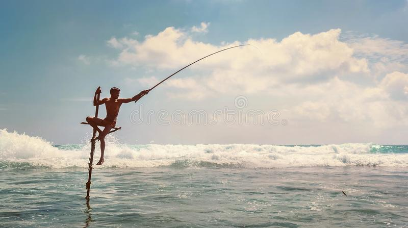 Sri Lanka traditionelles ` Stock ` - Methodenfische anziehender Fischer im Indischen Ozean bewegt wellenartig stockfoto