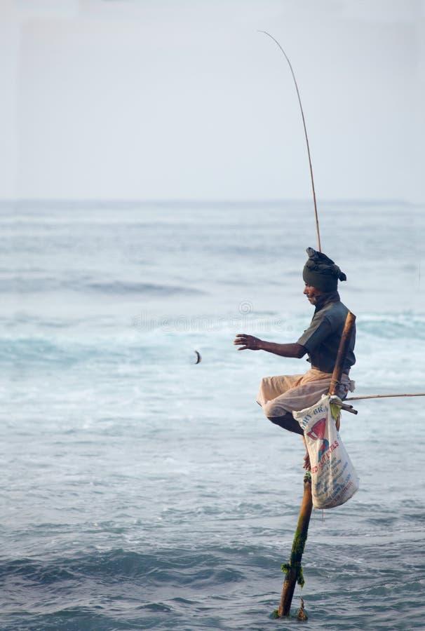 Sri Lanka traditionnel : pêche d'échasse en ressac d'océan photo stock