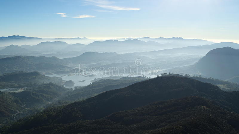 Panoramic view from Adam's Peak mountain on sunrise. Mountain range landscape with fresh morning colors. View from Sri Pada peak (Adam's Peak) stock photo