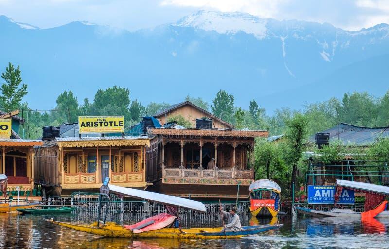Srinagar, la India - 25 de abril de 2017: Forma de vida en el lago Dal, gente que vive en 'barco de casa 'y que usa el bote peque foto de archivo libre de regalías
