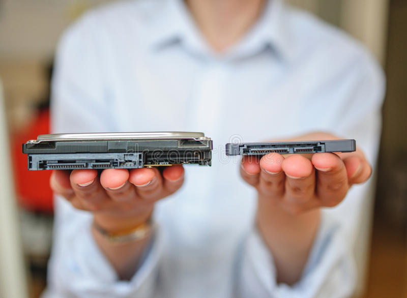 SSD vs HDD. Hands holding fast flash SSD - solid state drive and Hard Drive Disk HDD royalty free stock image