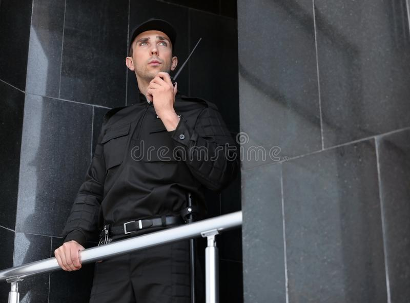 Ssecurity guard using portable radio transmitter outdoors. Male security guard using portable radio transmitter outdoors royalty free stock photo