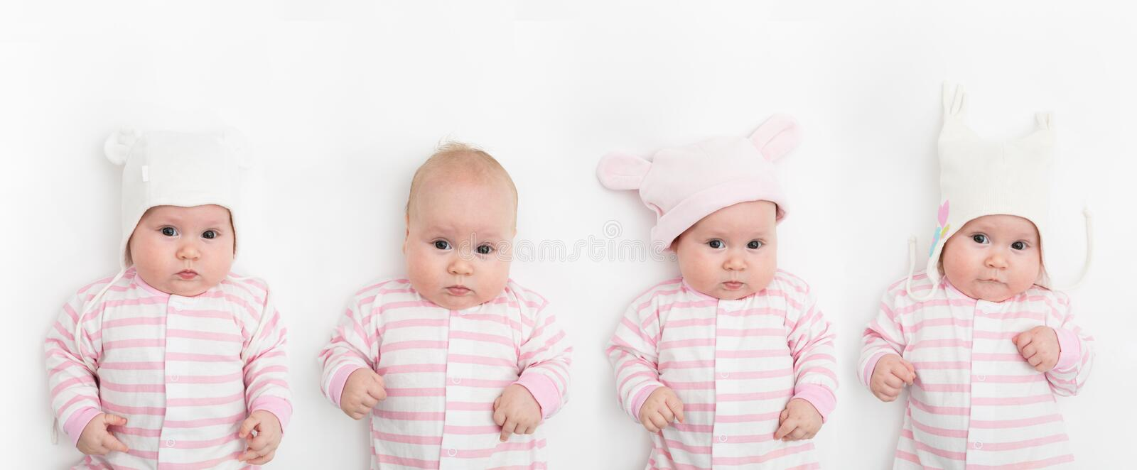 Cute adorable baby child with different warm white and pink hats. Happy baby girl on white background and looking at the royalty free stock photos