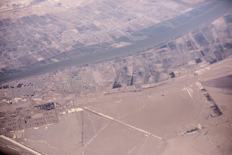Städer längs Iran, Irak gräns längs den Shatt Al Arab floden med oljeutsläpp i förgrund royaltyfri foto