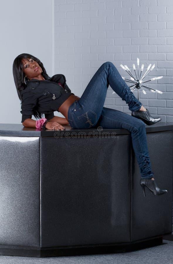 Städtische Afroamerikanerfrau, die auf Tabelle liegt lizenzfreie stockbilder