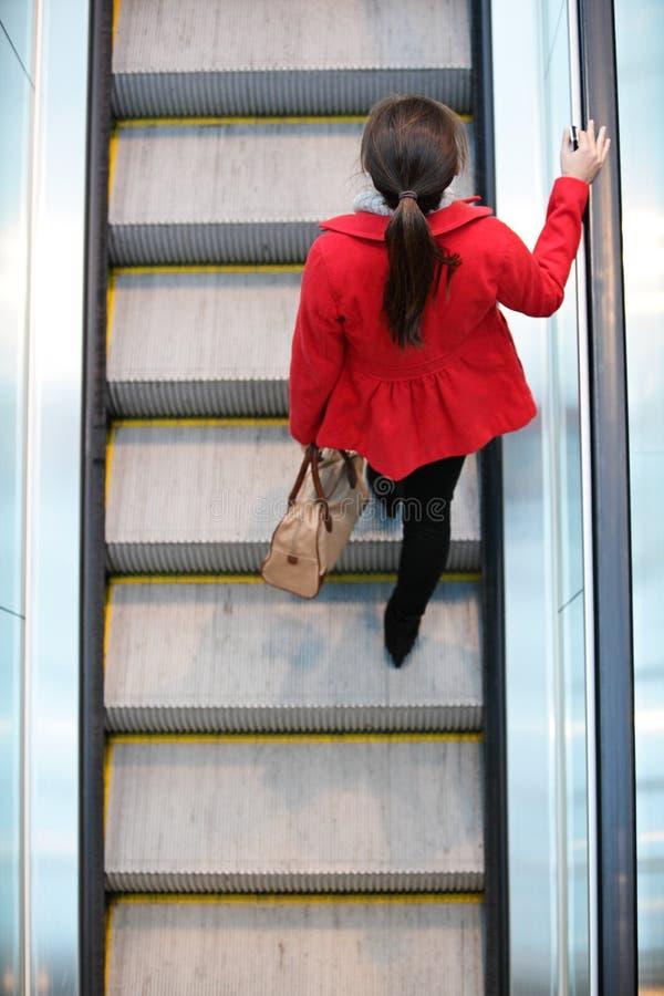 Städtische Leute - Frauenpendler, der auf Rolltreppe geht stockbild