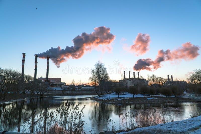 Städtische Naturstadtlandschaft mit Pfeifen des Wärmekraftwerks gegen blauen Himmel stockbilder