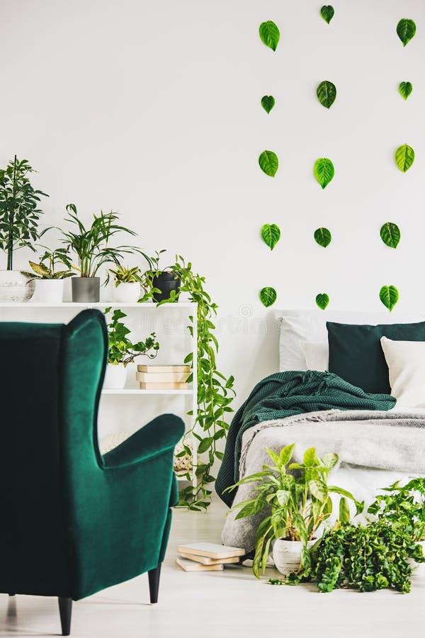 Städtischer Dschungel im modischen Schlafzimmer Innen mit weißer Bettwäsche und grüne Kissen und Decke lizenzfreies stockbild