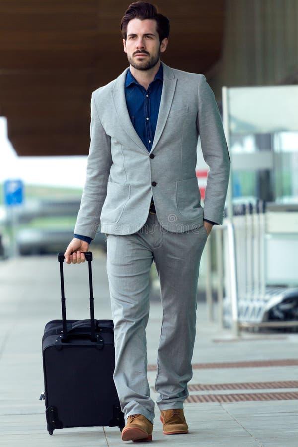 Städtischer Geschäftsmann mit einem Koffer gehend draußen in Flughafen lizenzfreies stockbild