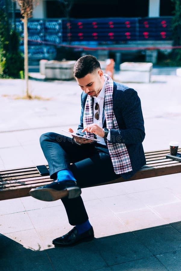 Städtischer Geschäftsmann sitzt auf der Bank im Stadtzentrum, lo stockfoto
