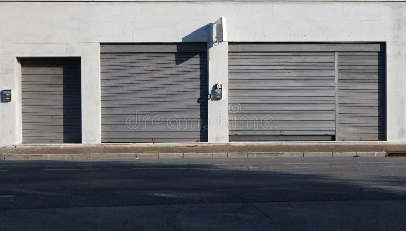 Städtischer Hintergrund Shopeinzelhandel mit Metallfensterläden schloss auf dem Bürgersteig an der Seite der Straße lizenzfreie stockfotografie