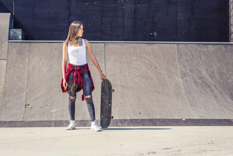 Städtischer Mädchenskateboardfahrer in der Skateboardanlage stockfoto