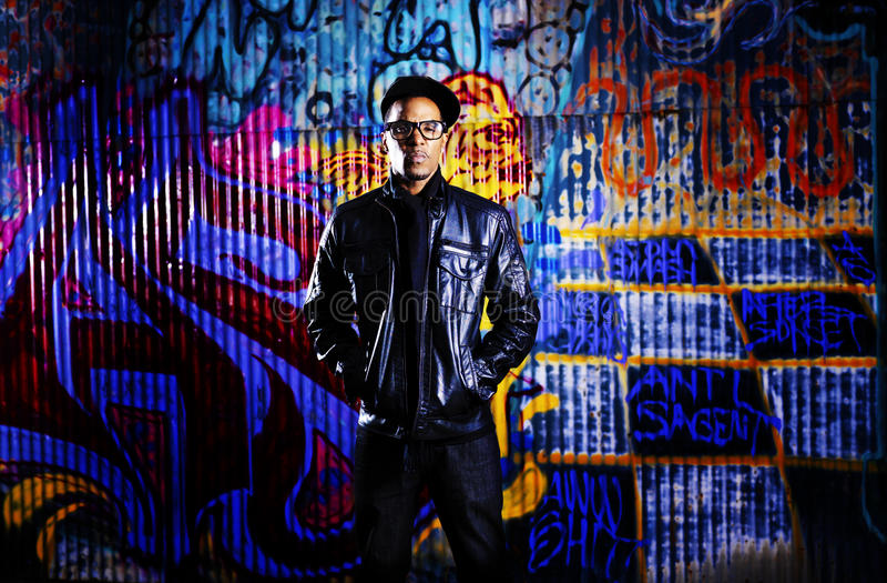 Städtischer Mann vor Graffitiwand. lizenzfreie stockbilder