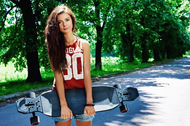 Städtisches Mädchen mit longboard lizenzfreie stockbilder