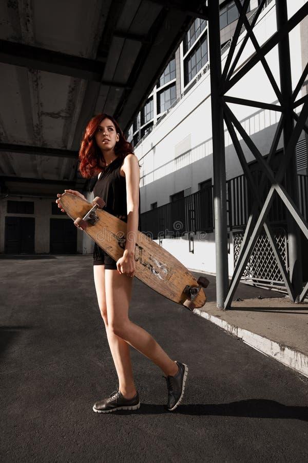 Städtisches modernes Mädchen mit dem longboard, das draußen in der Stadt aufwirft stockfotos