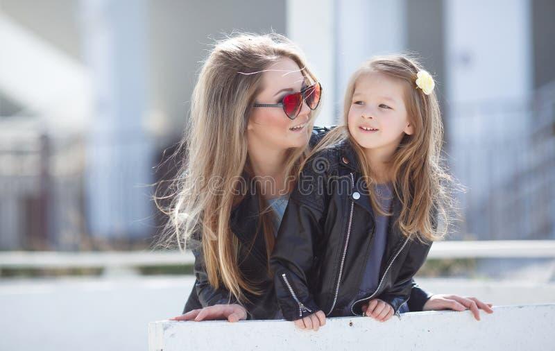 Städtisches Porträt der glücklichen Mutter mit kleiner Tochter stockbild