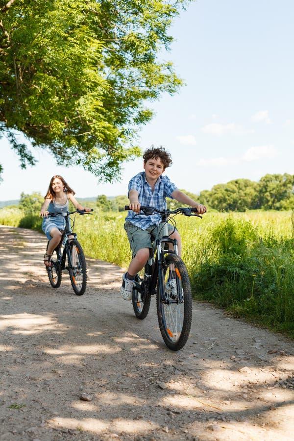 Städtisches Radfahren - Kinder, die Fahrräder reiten stockbilder