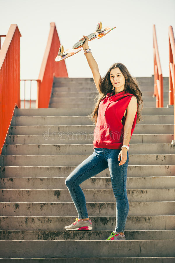 Städtisches Rochenmädchen mit Skateboard stockfotos