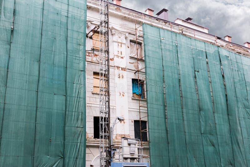 Städtisches Wohngebäude bedeckt mit einem grünen Stoff während überholten stockbild