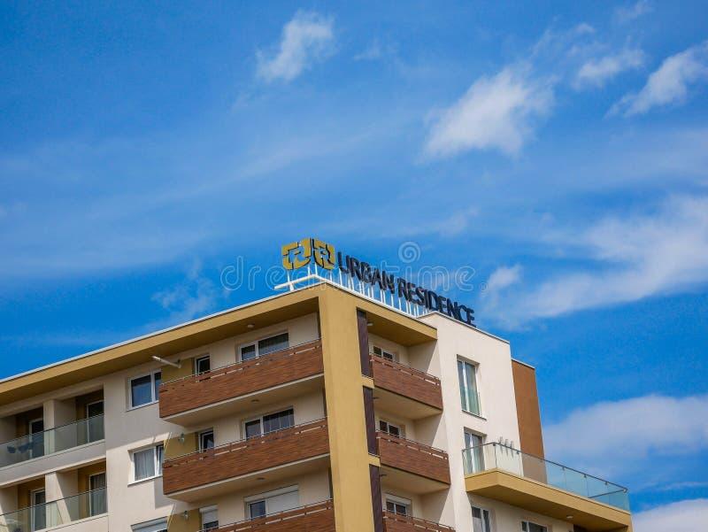 Städtisches Wohnsitzgeschäftslogo auf neuer, moderner Wohngebäudedachspitze lizenzfreies stockbild