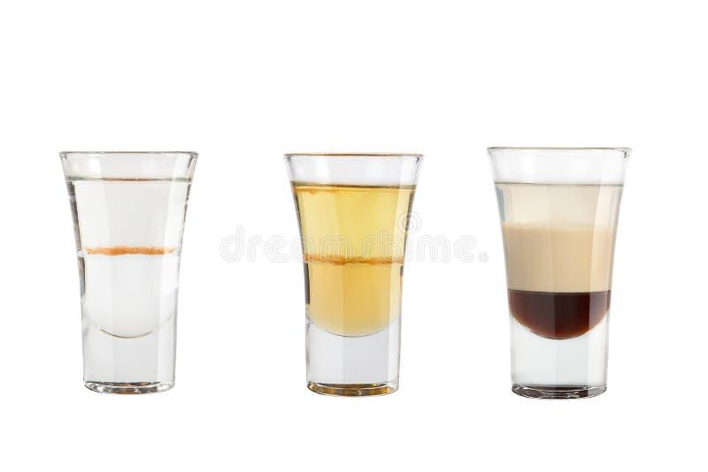 Ställ in av alkoholskott på en vit bakgrund Tre skott är olika royaltyfria bilder