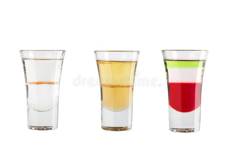 Ställ in av alkoholskott på en vit bakgrund Tre skott är populära arkivfoton