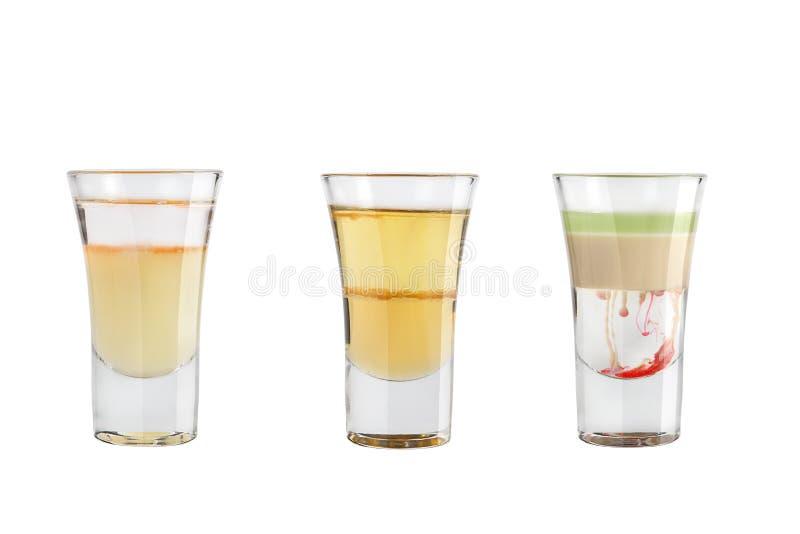 Ställ in av alkoholskott på en vit bakgrund Tre skott av alkoholiserat populärt arkivfoto