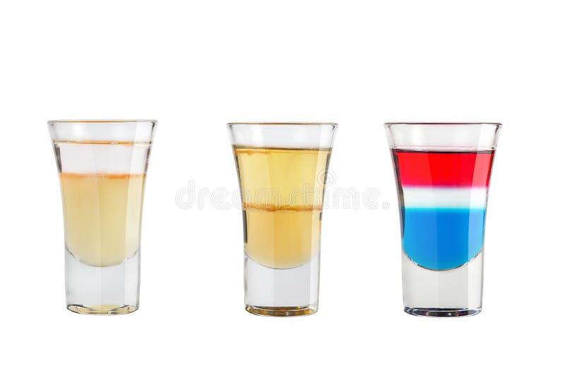 Ställ in av alkoholskott på en vit bakgrund Tre skott av populär alkoholist arkivfoton