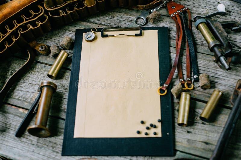 Ställ in av att jaga utrustning på tappningskrivbordet Jaga bältet med kassetter och skrivplatta med papper på träbakgrund arkivbilder