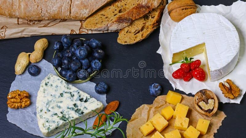 Ställ in av autentisk fransk ost - camembert, Dorblu, Brie Ost på en platta med örter, frukter och muttrar Foto för menyn av res arkivfoto